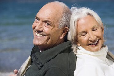 Germany, Bavaria, Senior couple relaxing on lakeshore, back to back, close up, portrait - WESTF10145