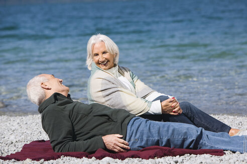 Germany, Bavaria, Walchensee, Senior couple relaxing on lakeshore - WESTF10139