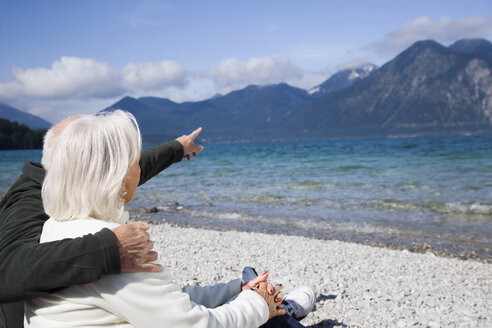 Germany, Bavaria, Walchensee, Senior couple relaxing on lakeshore, rear view - WESTF10136