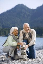 Germany, Bavaria, Walchensee, Senior couple piling up stones - WESTF10123