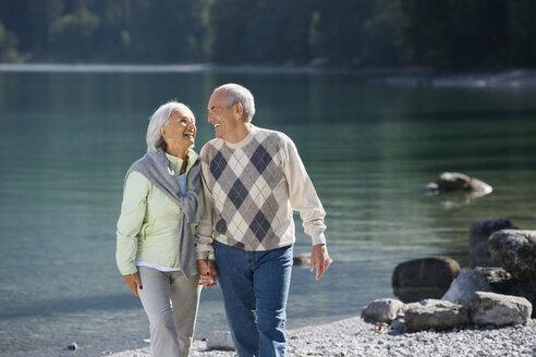 Germany, Bavaria, Walchensee, Senior couple walking across lakeshore - WESTF10114