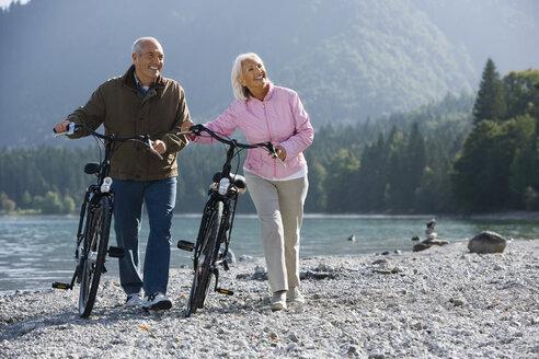 Germany, Bavaria, Walchensee, Senior couple pushing bikes across lakeshore - WESTF10108