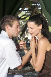 Young couple flirting, holding wine glasses, close-up - ABF00481