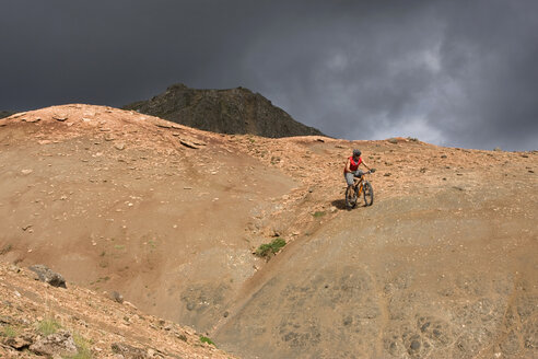 Iceland, Man mountain biking in hilly landscape - FF00979