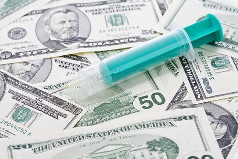 US Dollar bills, Syringe placed on top, close up - MAEF01370