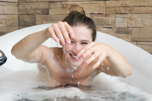 Young woman in bathtub fooling about - NHF01081