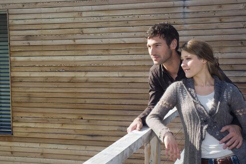 Young couple on balcony, portrait - NHF01054