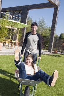 Young man pushing woman in wheelbarrow - NHF01048