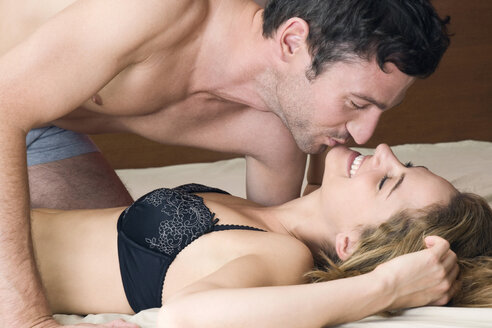Young couple kissing in bed - NHF01036
