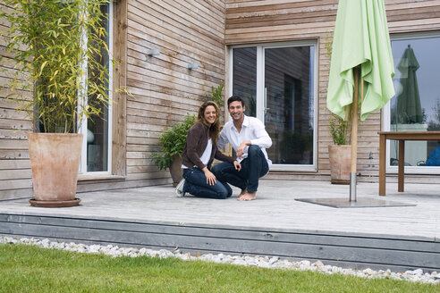 Germany, Bavaria, Munich, couple on terrace in front of house - NHF01018