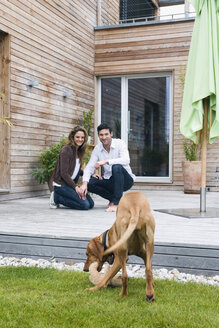 Germany, Bavaria, Munich, couple on terrace in front of house with dog - NHF01015