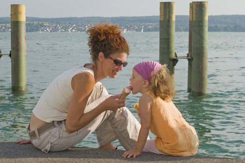 Germany, Baden-Württemberg, Lake Constance, Mothee an daughter (4-5) eating ice cream - SHF00275