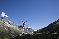 Switzerland, Wallis Alps, Mont Collon, Woman with walking sticks, cheering - GWF00937