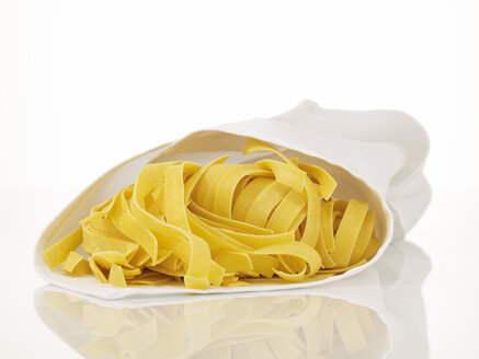 Uncooked pasta wrapped in dish towel, close-up - AKF00101