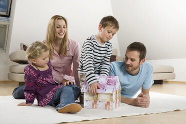 Family relaxing at home,Boy building house from Euro notes - CLF00677