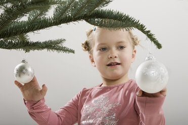 Little girl (3-4) looking at Christmas bauble - CLF00632