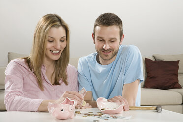 Young couple counting money, broken piggybank on table - CLF00626
