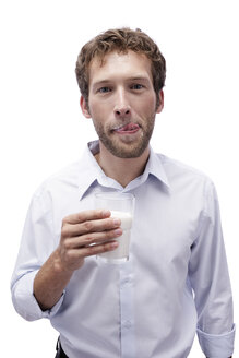 Young man holding a glass of milk, portrait - BMF00562