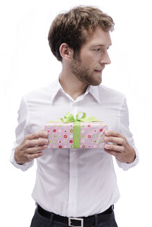 Young man holding gift box, portrait - BMF00544