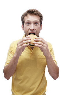 Young man eating Hamburger, portrait - BMF00532