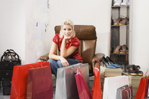 Young woman in shoe shop, shopping bags in foreground - WESTF11140