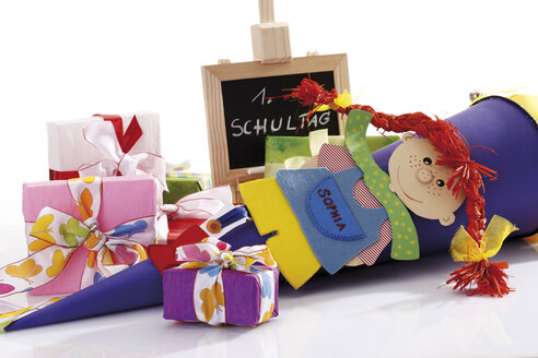 Colourful school cone and gift parcels next to chalkboard, close up - 10822CS-U