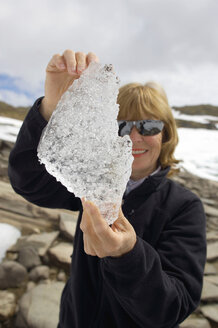 Norway, Fjord Norway, Woman holding piece of ice - MR01136