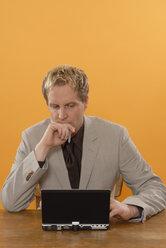 Businessman sitting at laptop, musing, portrait - KJF00030