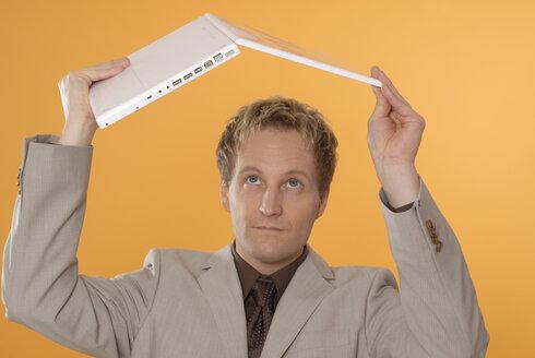 Businessman lifting laptop, looking ckeptical - KJF00027