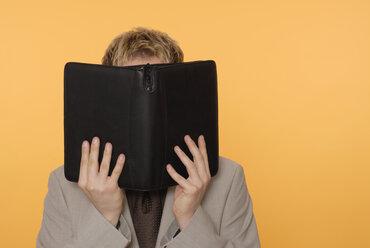 Man hiding face behind organizer - KJF00024