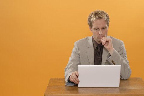 Man sitting at laptop, musing, portrait - KJF00021