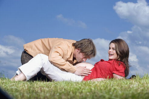 Woman lying in meadow, man kissing belly of pregnant woman, portrait - RDF00959