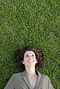 Young business woman lying on lawn, smiling, elevated view - KJF00062