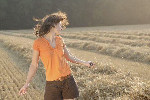 Young woman in field, dancing, listening to MP3 player - KJF00053