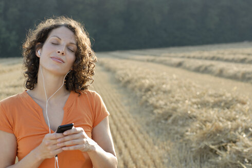Young woman in field listening to MP3 player, portrait - KJF00050