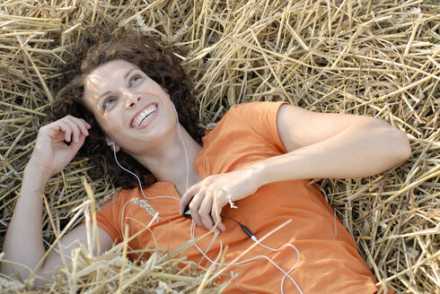 Young woman with MP3 player  relaxing in hay, smiling, portrait - KJF00047