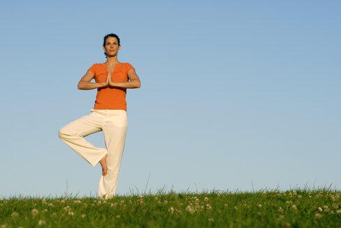 Woman doing a yoga balance pose - KJF00044
