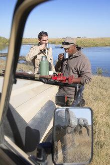Africa, Botswana, Okavango Delta, Men on safari having a break - PK00344
