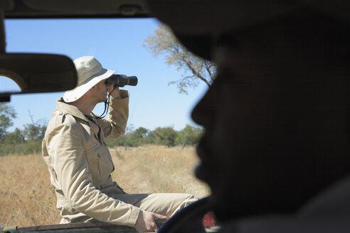 Africa, Botswana, Man looking through binoculars - PK00341