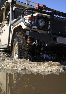 Africa, Botswana, Okavango Delta, Vehicle driving through water - PK00332