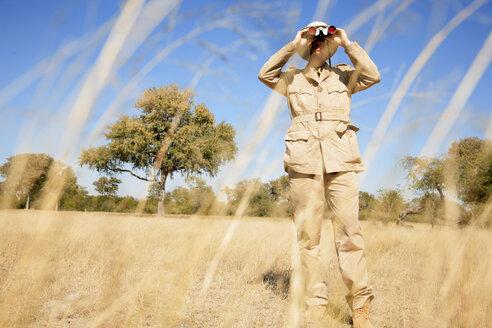Africa, Botswana, Okavango Delta, Man looking through binoculars - PK00320