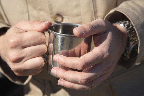 Africa, Botswana, Man holding mug, close-up - PK00317