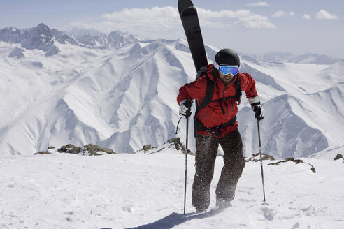 India, Kashmir, Gulmarg, Man with skis on back going uphill - FFF01054