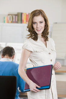 Germany, Munich, young woman in office, man working in background - LDF00667