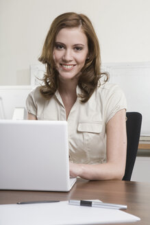 Germany, Munich, young woman in office, using laptop, smiling, portrait - LDF00652
