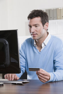 Germany, Munich, business man in office holding credit card, portrait - LDF00637