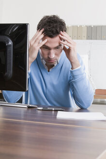 Germany, Munich, business man at desk, hands on head - LDF00634