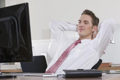 Germany, Munich, business man relaxing in office - LDF00625
