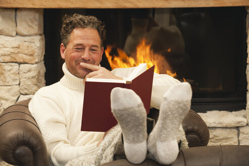 Man in front of fire place reading a book, portrait - WEST11579