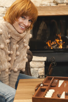 Woman sitting in front of fire place, smiling, backgammon board in foreground - WEST11555